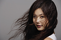 Head shot of Chinese woman with wind blown hair - Asia Images Group