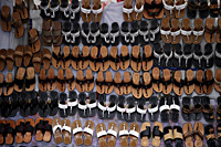 Many leather sandals on display at market. - Asia Images Group