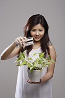 Chinese woman watering a green plant - Asia Images Group