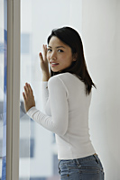 Young Asian woman looking out window - Asia Images Group