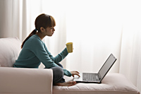 Asian girl at home on laptop - Asia Images Group