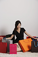 Chinese woman sitting on floor with shopping bags - Asia Images Group