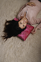 Chinese woman laying on pink pillow - Asia Images Group