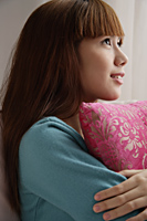 Asian girl holding pink pillow, looking up - Asia Images Group