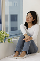 Young Asian woman looking out a window - Asia Images Group