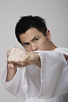 Head shot of Chinese man punching, martial arts - Asia Images Group