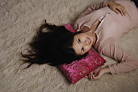 Chinese woman laying on rug - Asia Images Group