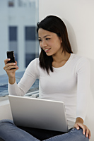 Young Asian woman looking at phone with laptop on lap - Asia Images Group