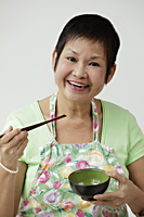 Mature Chinese woman holding chopsticks and bowl - Asia Images Group