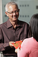 "older man passing red envelopes ""hong bao"" to woman - Asia Images Group"