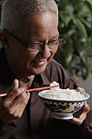 profile of mature man holding chopsticks and bowl of rice - Asia Images Group