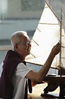 mature man working on model sail boat and smiling - Asia Images Group