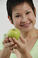 Mature Chinese woman holding green apple and smiling - Asia Images Group