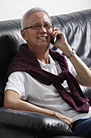 older man talking on phone and smiling - Asia Images Group