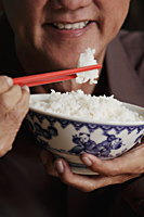 cropped shot of mature man holding chopsticks and bowl of rice - Asia Images Group