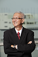 mature man wearing a suit smiling with arms crossed - Asia Images Group