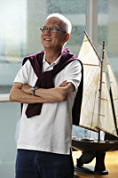 mature man folding his arms and smiling in front of model sail boat - Asia Images Group