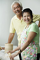 Chinese couple cooking together and smiling - Asia Images Group