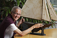 older man with model sail boat - Asia Images Group