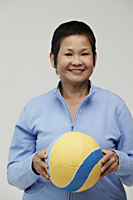 Mature Chinese woman holding a volleyball - Asia Images Group