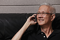 head shot of mature man with grey hair talking on phone - Asia Images Group