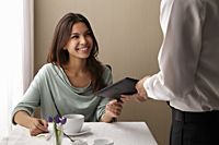 Young woman paying the check at a restaurant - Asia Images Group