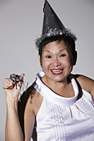 Mature Chinese woman wearing a party hat and smiling - Asia Images Group