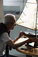 profile of older man working on model sail boat - Asia Images Group