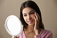 young woman looking at mirror touching her face - Asia Images Group