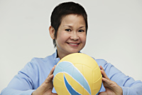 Mature woman holding a volleyball and smiling - Asia Images Group
