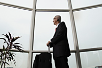 mature man looking out the window and holding luggage - Asia Images Group