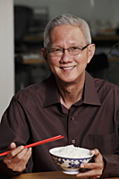 mature man holding chopsticks and bowl of rice and smiling - Asia Images Group