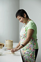 Mature Chinese woman making Dim Sum - Asia Images Group