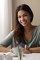 young woman at a cafe, smiling looking at camera - Asia Images Group