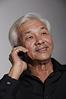 Mature Chinese man talking on phone - Asia Images Group