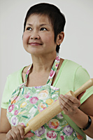 Mature Chinese woman holding rolling pin - Asia Images Group