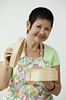 Mature Chinese woman holding bamboo steamer - Asia Images Group