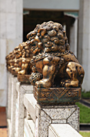 Row of bronze lions in front of temple - Asia Images Group