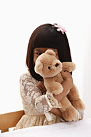 young girl holding teddy bear in front of her face - Asia Images Group