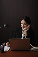 Chinese woman sitting at her desk and talking on phone. - Asia Images Group