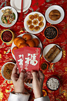 Hands holding red envelopes (Hong Bao) over table with Chinese food. - Asia Images Group
