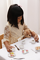 young girl having a tea party with her teddy bear - Asia Images Group
