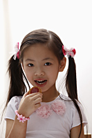 Young Chinese girl eating a cookie - Asia Images Group
