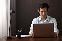 man sitting at desk working on laptop - Asia Images Group