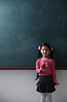 Young girl holding red apple in front of chalk board - Asia Images Group