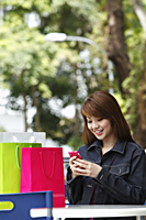 Young woman sitting outside with shopping bags and looking at phone - Asia Images Group