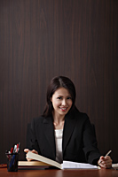 woman working and smiling at her desk - Asia Images Group