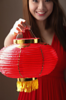 Young woman holding red lantern and smiling - Asia Images Group