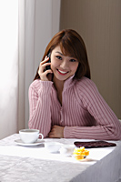 Young woman sitting at table with coffee and talking on phone - Asia Images Group