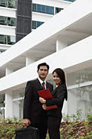 man and woman wearing suits standing in front of building - Asia Images Group